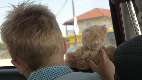 Little child with teddy bear looking out car window Footage