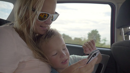 Child playing with mothers smartphone in the car Footage