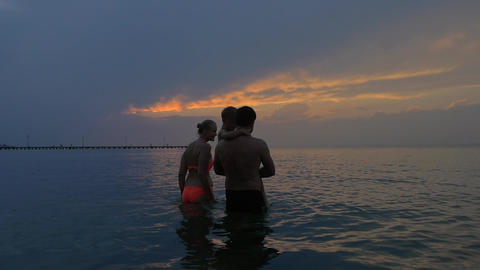 Family with child in the sea at twilight Footage