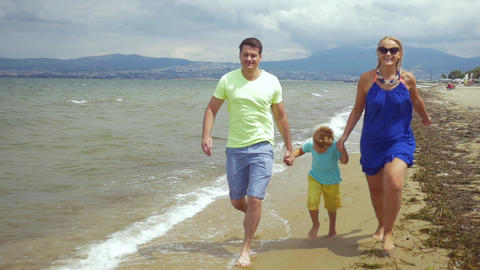 Barefoot family of three running along the sea Footage