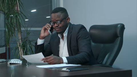 Afro-american businessman examining charts and talking on the phone Footage