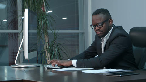 Handsome afro-american businessman working and typing on laptop in the office Footage