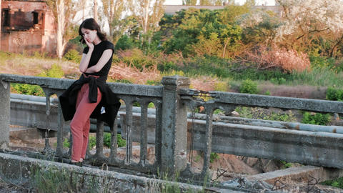 A view from right to left of a sad woman, standing on a bridge, who sadly covers Footage
