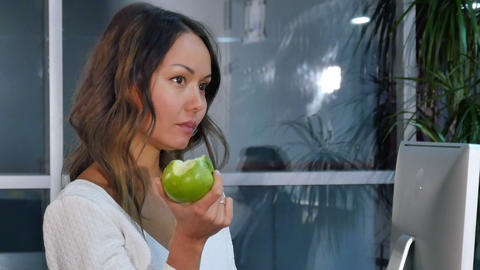 Pretty businesswoman eating green apple in the office Footage