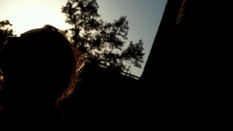 A silhouette of a young woman touches her hair emotively, with the feeling of Live Action