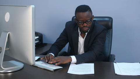 Portrait of young serious afro-american businessman working with laptop and Footage