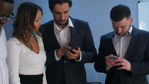 Group of five multiracial business people standing and using smartphones Footage