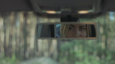 Reflection of cute woman in car rear-view mirror Footage