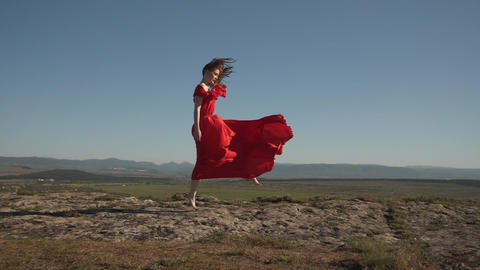 woman model in scarlet fluttering in the wind dress and barefoot Live Action