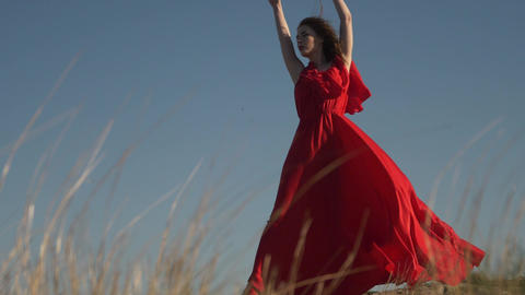 young female model in scarlet flowing in the wind dress and barefoot posing Live Action