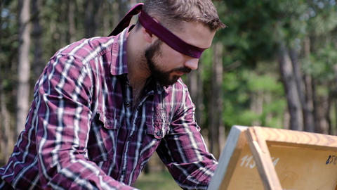 A blindfolded man is passionately working on his picture , being in the woods Live Action
