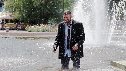 A man is walking in a fountain, covering his face with hands and feeling all the Live Action
