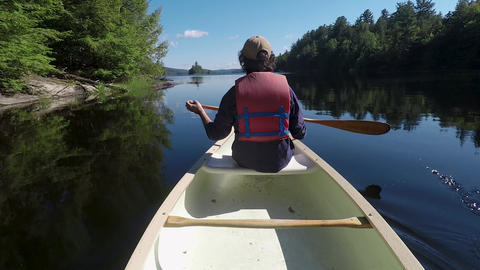 Man wearing a personal floatation device paddling from the front of a canoe in a Footage