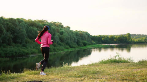 A morning jog in the Park near the pond in the Sunny rays of dawn, the girl is Live Action