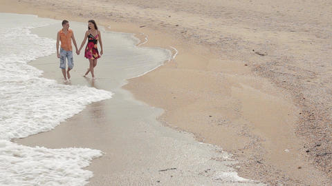 a pair of lovers walking along the sand in the surf line Live Action