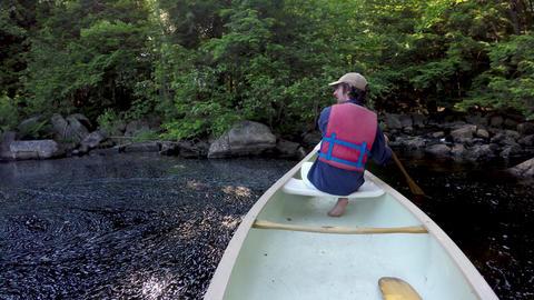 Man paddling a canoe along the edge of a river or mountain lake GIF