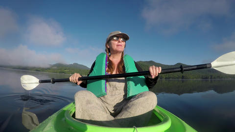 Attractive woman in her 40s or 50s resting in a kayak enjoying the view of the Footage