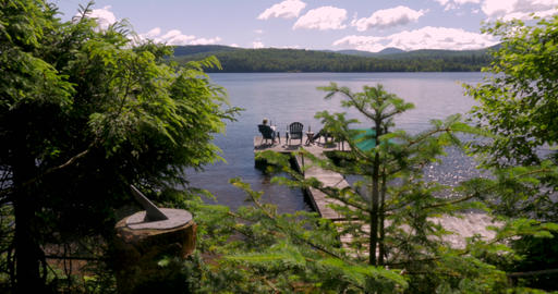 Two people relaxing on a dock along a mountain lake with a sun dial in view in Footage
