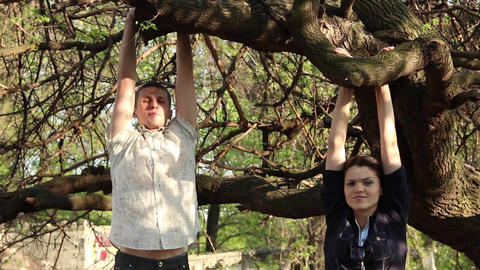 young man and woman are hanging on a tree with hands on a branch GIF