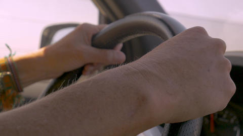 Close up of two hands of a woman wearing friendship bracelets holding a steering Live Action