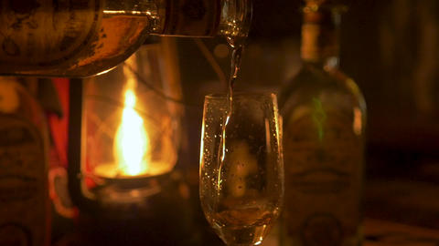 Close up of a person pouring tequila in a champagne flute lit by lantern in a Live Action