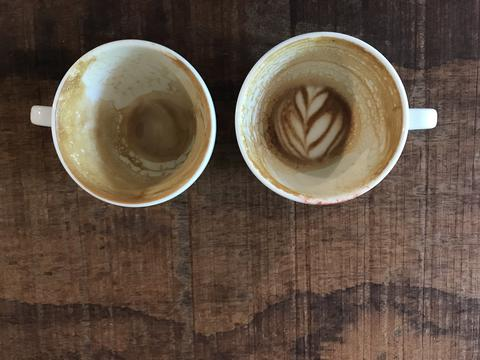 two cups of finished hot latte coffee with leftover latte art フォト