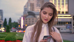 Young beautiful girl is typing message on her smartphone at sunset in city Footage