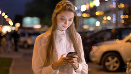 Young attractive girl is typing message on her smartphone in evening in city Footage