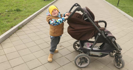 Baby boy playing with his stroller walking outdoor Footage