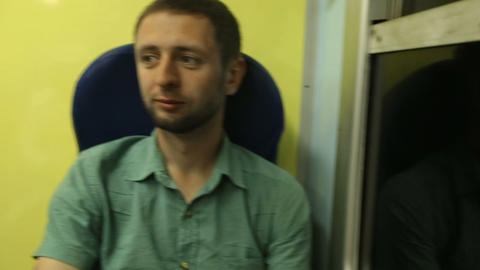 Male commuter sitting by the window on night train, his reflection in dark glass Footage