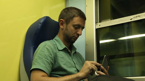 Guy using his mobile phone while traveling to another destination on night train Footage
