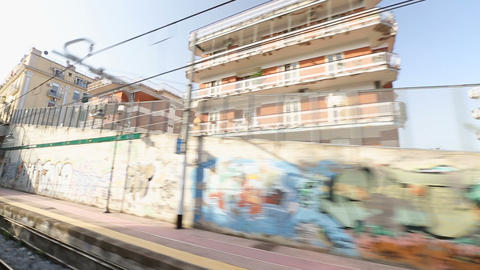 City train going through passageway with graffiti walls and buildings in Naples Footage