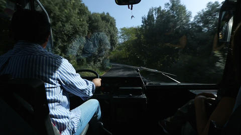 Man driving coach down narrow curvy road, view of road from windshield window Footage