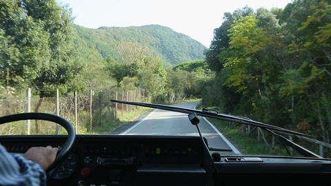 Coach going down narrow road aligned with plants, view from behind windshield Footage