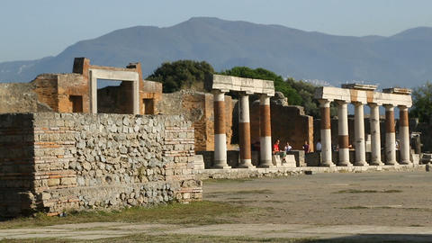 Broken row of ancient columns lining up square in Pompeii, people walking behind Footage