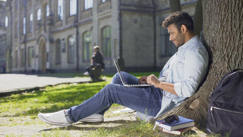 Multinational young man reading information on laptop under tree, surprised Live Action