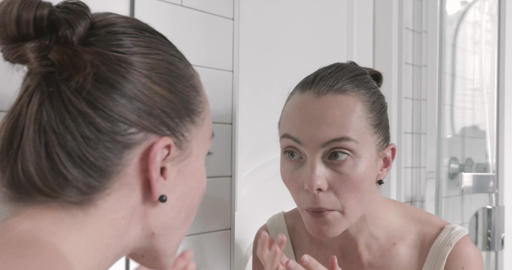 Beautiful young woman checking her face in mirror Footage