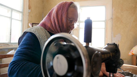 A woman sews on an old sewing machine. Slow motion Live Action