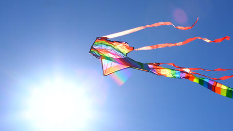 4k Colorful rainbow kite flying against a sunny blue sky handheld, soaring high Footage