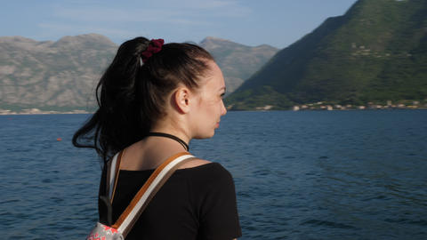 The camera revolves around a young woman who admires the sea and mountains Footage
