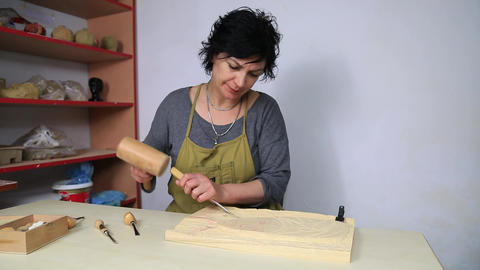 Sculptor in her atelier, cutting a block of wood to make a statue from scratch Footage