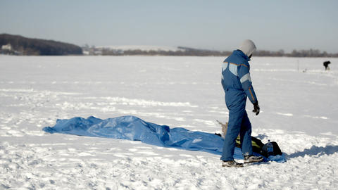 Winter fun. People on the frozen lake are engaged in paragliding and winter Live Action