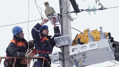 electrician unfixes fasteners on metal structure on winter day Live Action