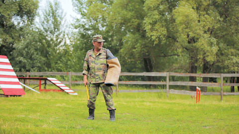 man in military uniform attacked by sheep dog GIF