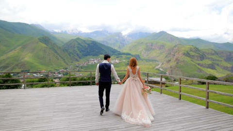 Happy newlyweds on a background of mountains on their wedding day. Wedding photo 影片素材