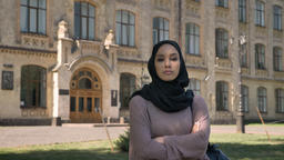 Young self-confident muslim girl is standing with arms crossed in daytime in Footage