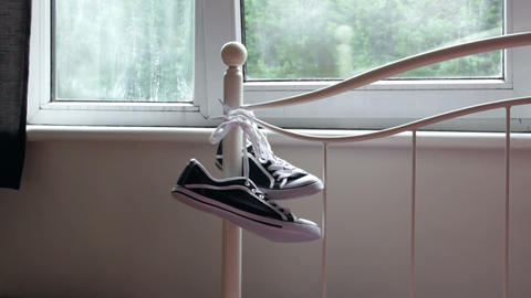 Pair of sneakers hanging on the bed rail by the window Footage