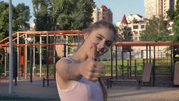 Young pretty woman giving thumbs-up to camera and smiling, outdoor gym on Footage