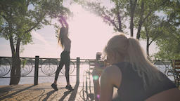 Blonde woman taking photos of her friend, other woman posing for photo Footage