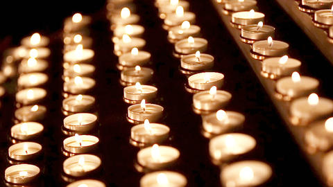 Lots of candles with shallow depth. Small candles on table in Catholic Church Footage